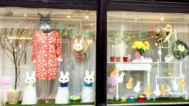 A fresh and clean window display, with a white background and a dressed rabbit for Easter.