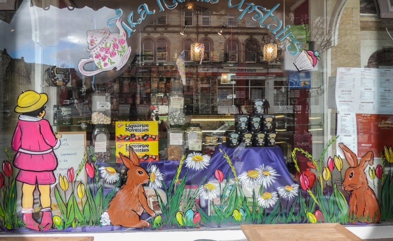 Beautiful painting for the Easter window display, with a girl staying near two rabbits in the grass and surrounded by flowers.