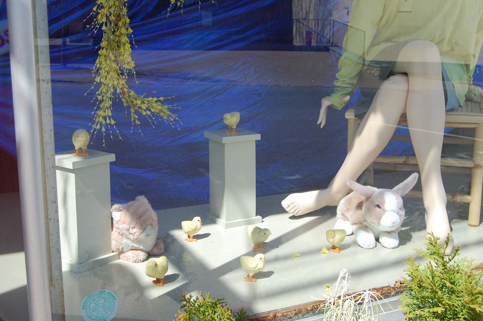 On a metallic blue background and a white floor, this window display made an Easter decoration with a sitting mannequin surrounded by a plush rabbit and a few little chicks.