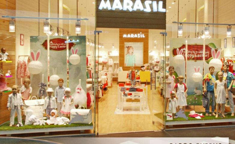 Marasil kids store is announcing Easter through the window display with white clothes and rabbit ears,