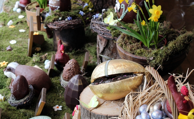 On a floor with moss, placed in the window display, the Easter is ready with surprise golden eggs, chocolate eggs and flowers.