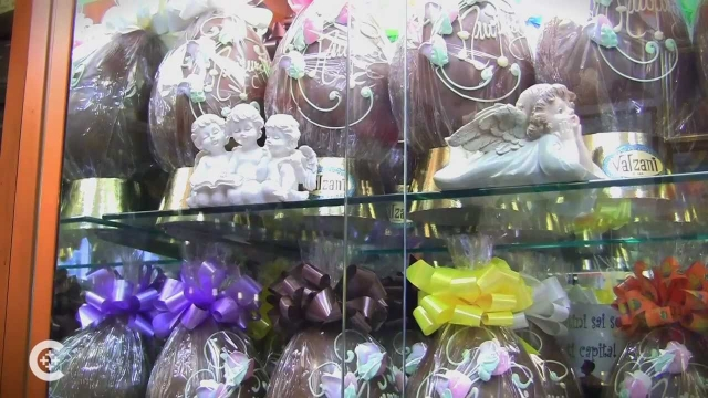 An Italian Easter window display with packed chocolate eggs, with yellow, purple and brown bows.
