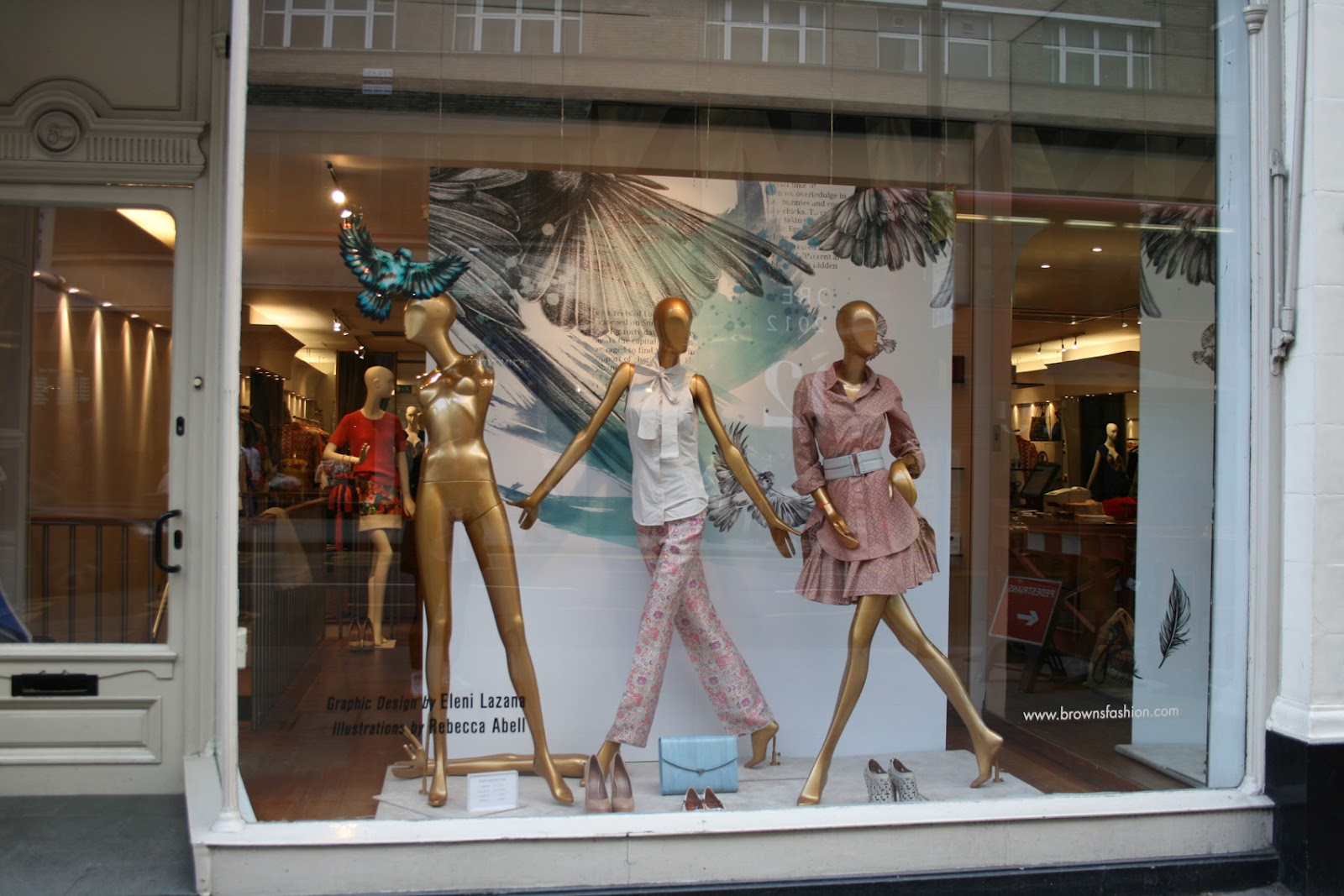 Positioned in the same way, three mannequins, dressed in pastel colors, a blue gorgeous bird and few accessories are placed in this window display for Easter.