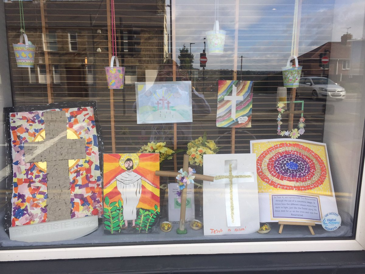 A religious window display with a painting of Jesus Christ and cross, proper for the Easter holiday.