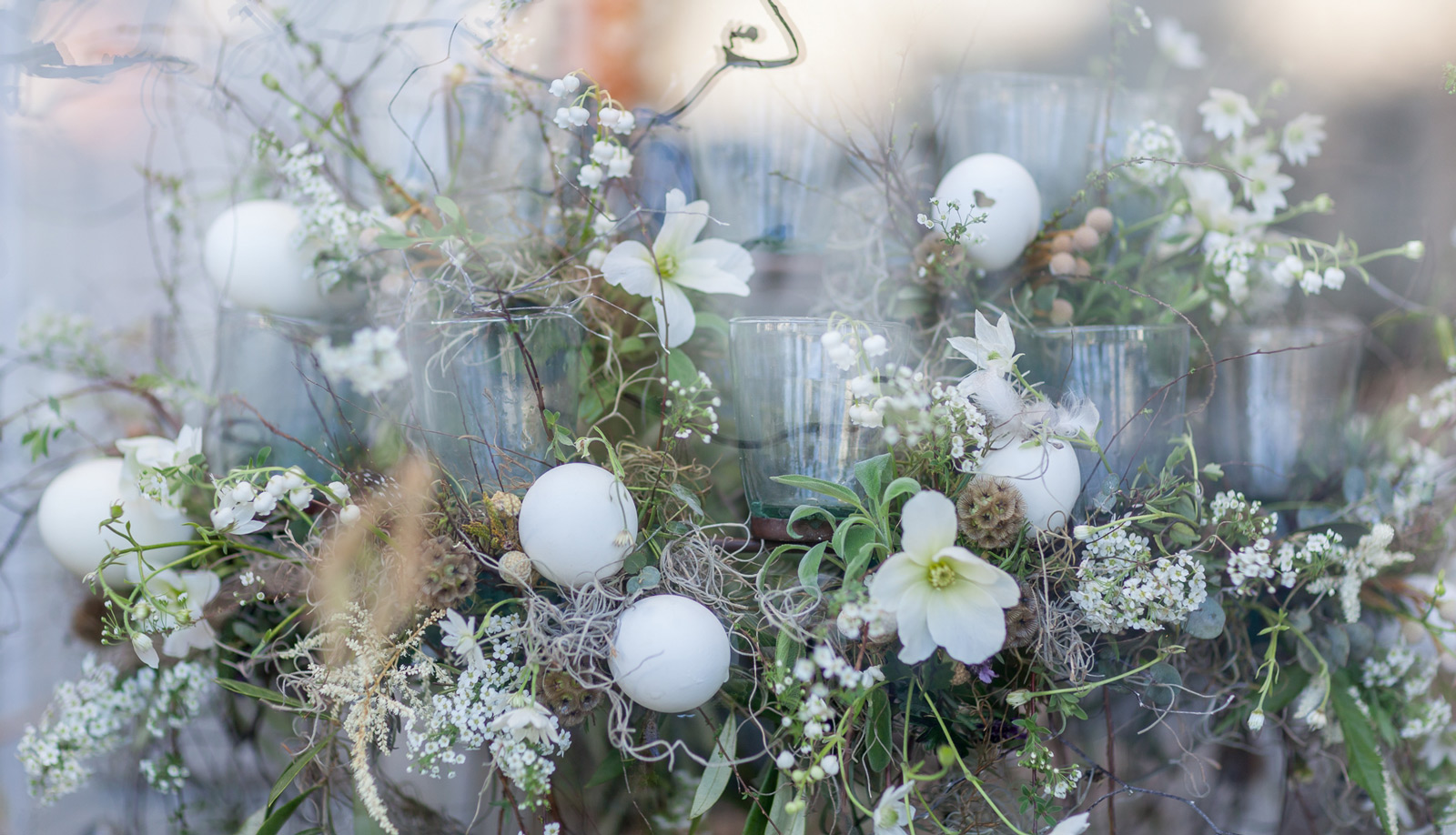 A window display with a simple touch and pure white eggs placed between flowers. A gentle touch of Easter.