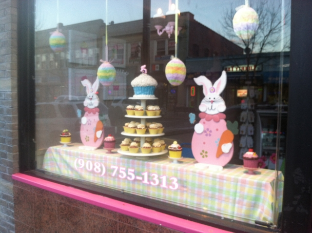 A sweets shop with cupcakes and bunnies in the window display and eggs hanging because it's Easter time.