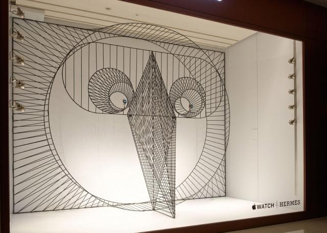 A Hermes window display focused on the Apple Watch, featuring geometric 3D minimalist motifs.