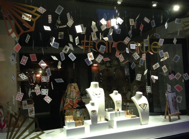 The #Arcade jewelry window display design using a playing / poker cards theme by hanging them from the top display area.