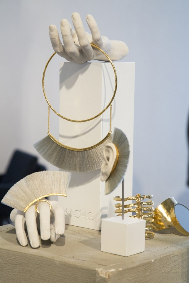 A minimalist white display from Bjorg using jewelry stands and mannequin jewelry display hands plus some jewelry that is brush themed.