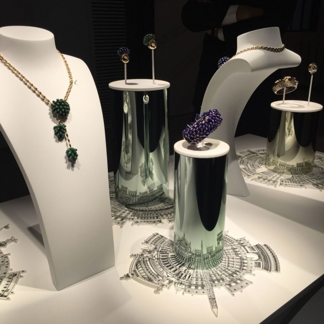 An absolutely stunning minimalist jewelry window display arrangement, featuring rounded mirrored jewelry risers, display busts and some architectural motifs that are reflected on the displays.