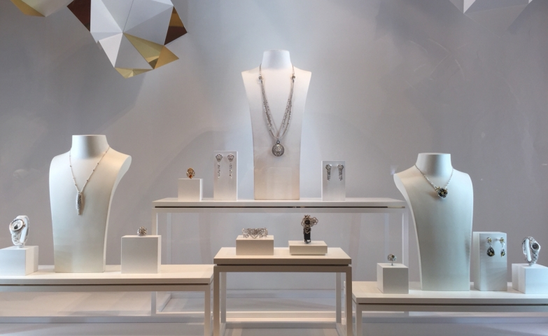 Chanel's fine jewelry window display is subtly organized and completely symmetrical. Minimalism works perfectly with the white jewelry displays: risers, busts and holders.