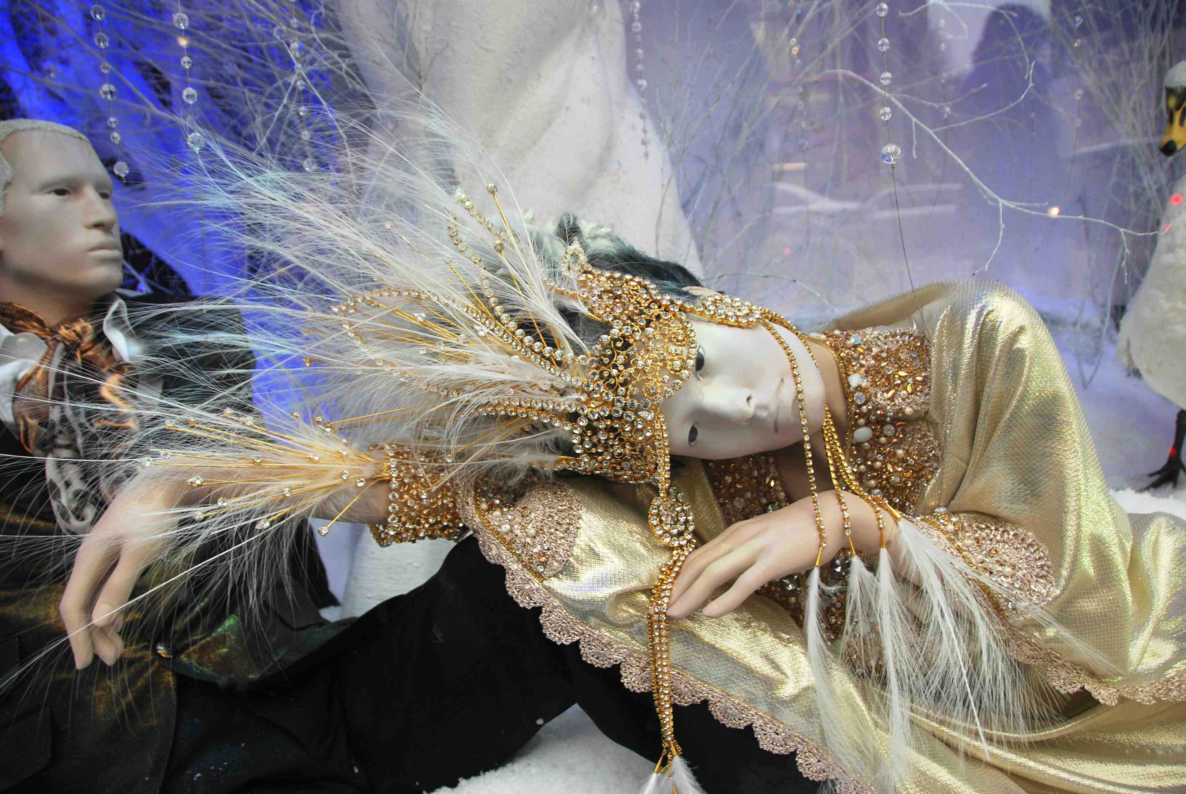 This Christmas jewelry window display features two realistic mannequins, one of them adorned in precious jewelry and gold thread clothing.