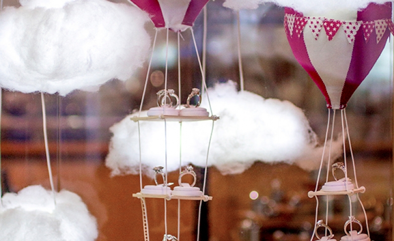 A creative jewelry window display at The Village Goldsmith featuring hot air balloons that are carrying little display props / ring holders over a tiny village model.