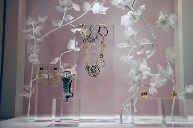 A creative jewelry window display focused on just a few items, including a watch, earrings, rings and necklace, using transparent jewelry displays and some beautiful background props shaped as flowers.