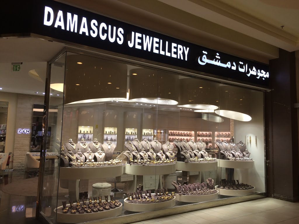 A tightly packed yet very neatly organized jewelry window display using lots of leatherettes, mannequin busts and risers to display jewelry at Damascus Jewellery.