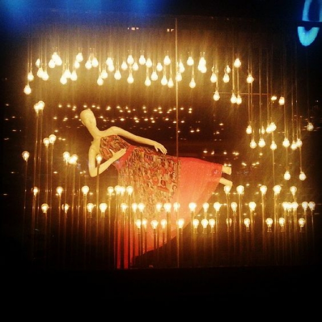 """""""A little art everyday"""" theme for window display with suspended mannequin and bright yellow light-bulbs."""