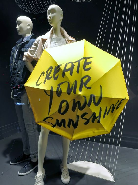 Mannequin merchandise display with a bright yellow umbrella from Banana Republic in London.