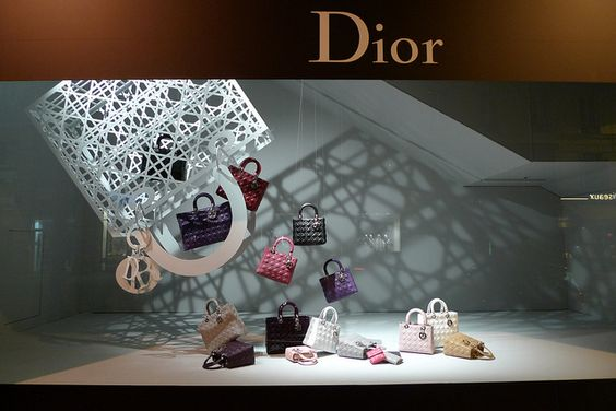 Beautiful display which plays with big geometric display props and shadows, window of Dior in Au Bon Marche, Paris, France.