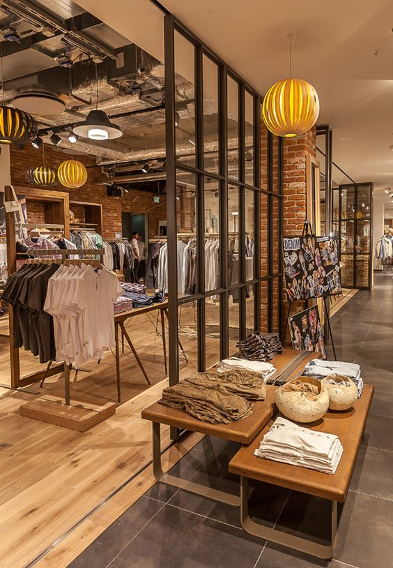 Classical brown tones, with a wooden core and falling illuminated globes, convey the feeling of relaxation and provide a more than satisfying shopping experience in this Esprite store.
