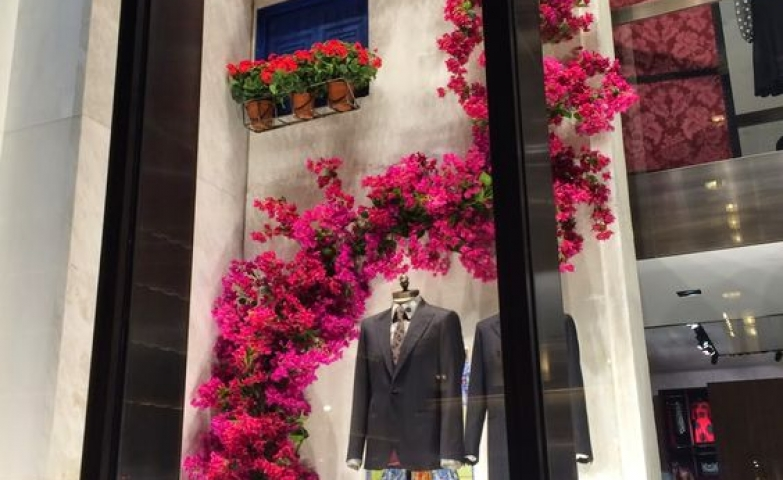Bright pink flowers and high white wall used for this window display by Dolce & Gabbana, New York.