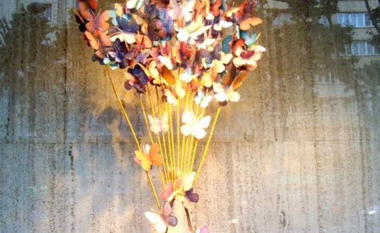 Loewe creative window display with butterflies pulling on a handbag seen in Avenida Diagonal, Barcelona.