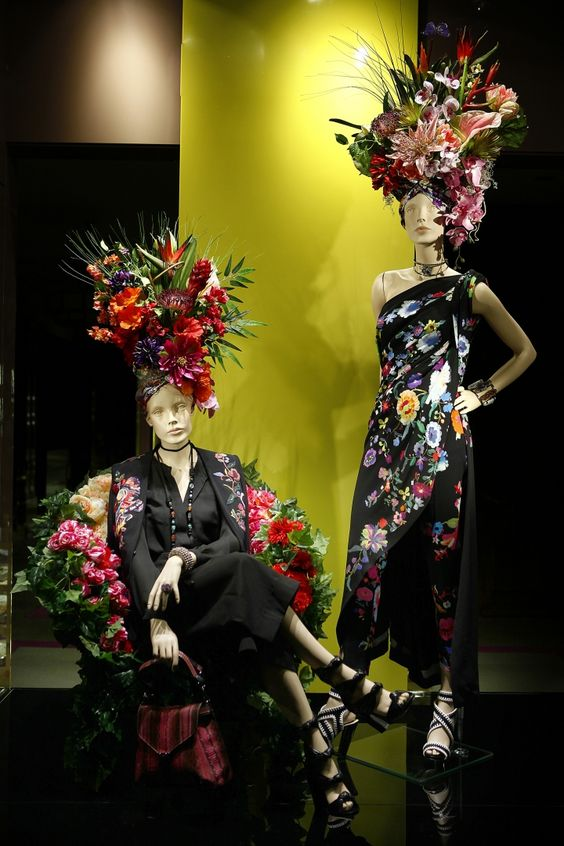 Visual merchandise display with mannequins and assorted flower arrangement to go with the exposed clothes.