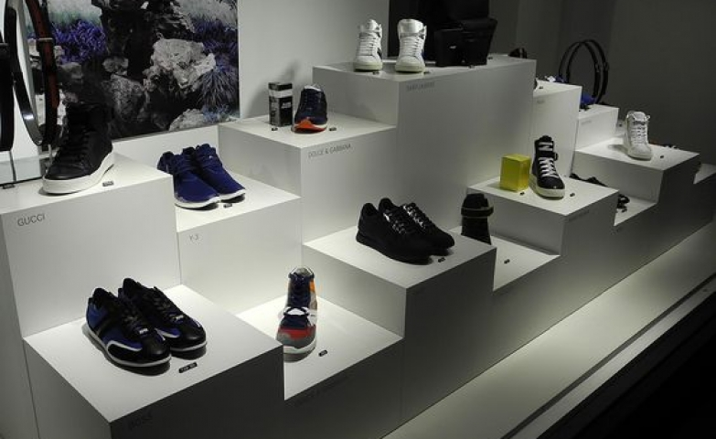 A white and minimalist shoe display, with a calming and balance picture hanging on the wall, that makes a nice contrast with the varied collection.