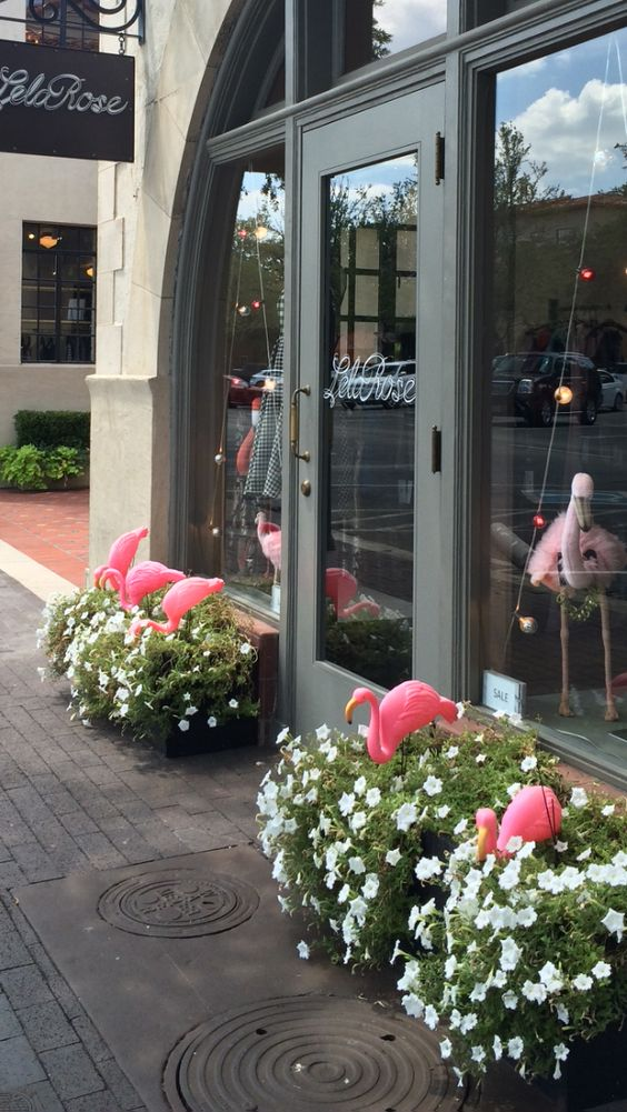 Summer window display by Lela Rosa with cute pink flamingos seen in Highland Park Village, Dallas.