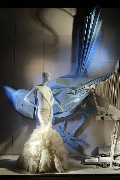 Visual merchandising display set with odd shapes and blue light for a white dress, seen in Barcelona.