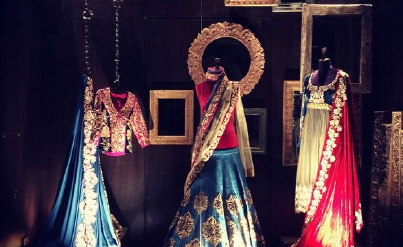 Stunning Indian clothing set combined with empty frames seen in an Indian window display.