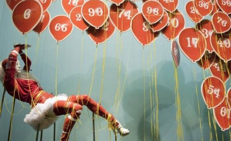 """Selfridges themed """"Guess the song"""" display in London with a mannequin suspended in mid air and surrounded by balloons."""