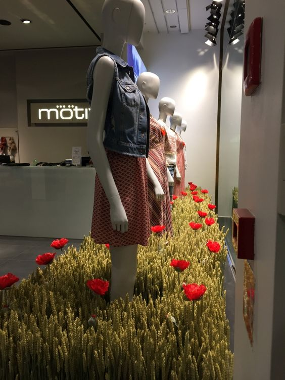 "Themed ""Food is fashion"", Motivi created a display placing the mannequins in a natural looking field of poppy flowers."