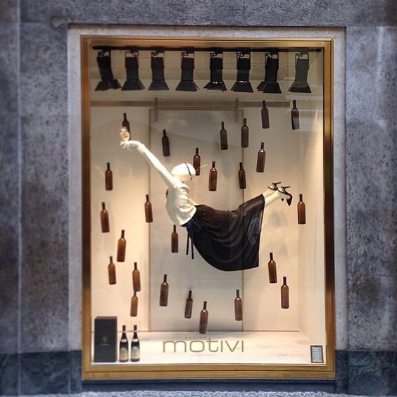 Window display with a mannequin floating in mid air, surrounded by glass bottles. Display for Motivi in Italy.