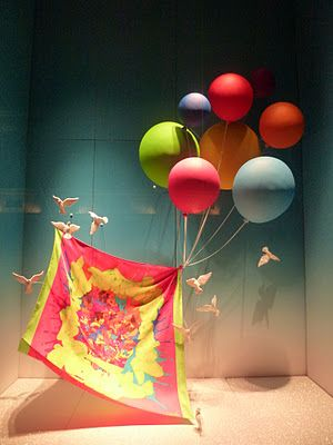 Colorful balloons and white doves props used to create a visual merchandising design for Hermes, in Paris.