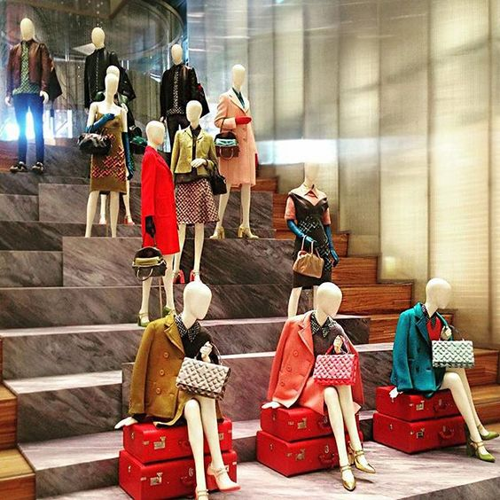 Amazing display from Prada with mannequins placed at different heights on steps and seated on bright red suitcases, seen in New York.