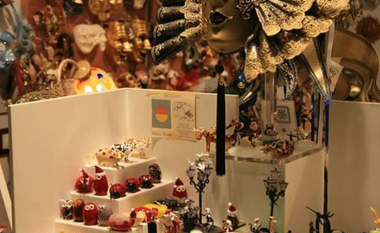 Golden Venetian mask and colorful souvenirs seen around shop windows in Italy.