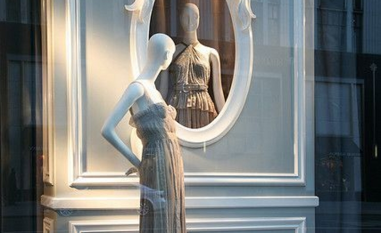 A wall with a mirror shape on it in which the mannequin sees itself, creating an elegant feminine display for Christian Dior, in Paris.