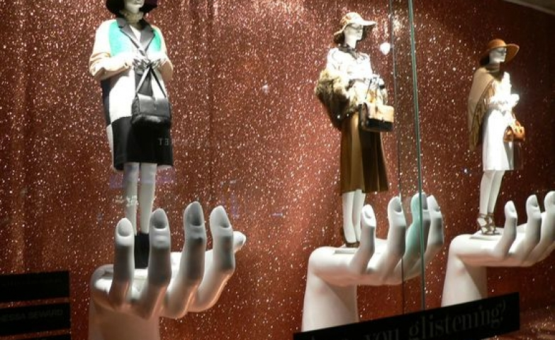 Fenwick display with giant hand shaped stands for the mannequins and a glitter background in London.