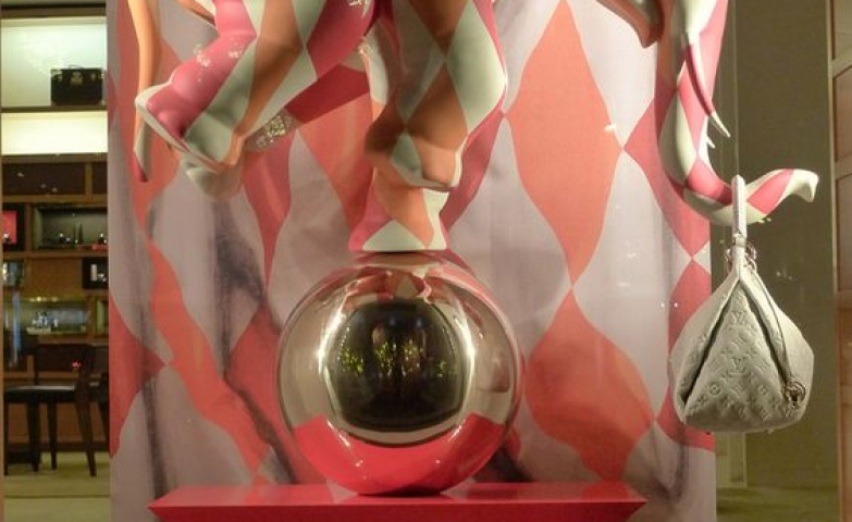 Visual merchandising display with circus theme showing an elephant on a mirrored sphere, window for Louis Vuitton.