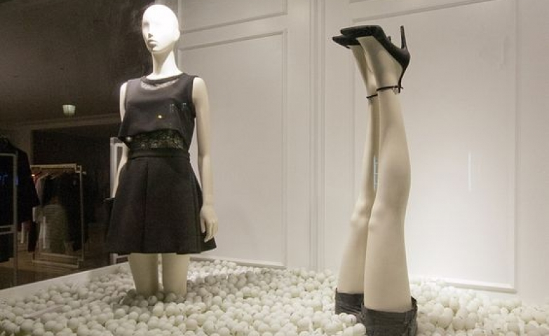 Interesting display using many white balls and two mannequins, with one displayed upside down and only showing the feet.