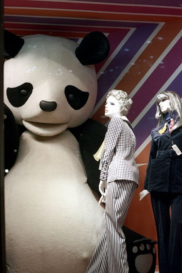 Surreal window display with giant panda bear and colored striped seen in Tokyo.