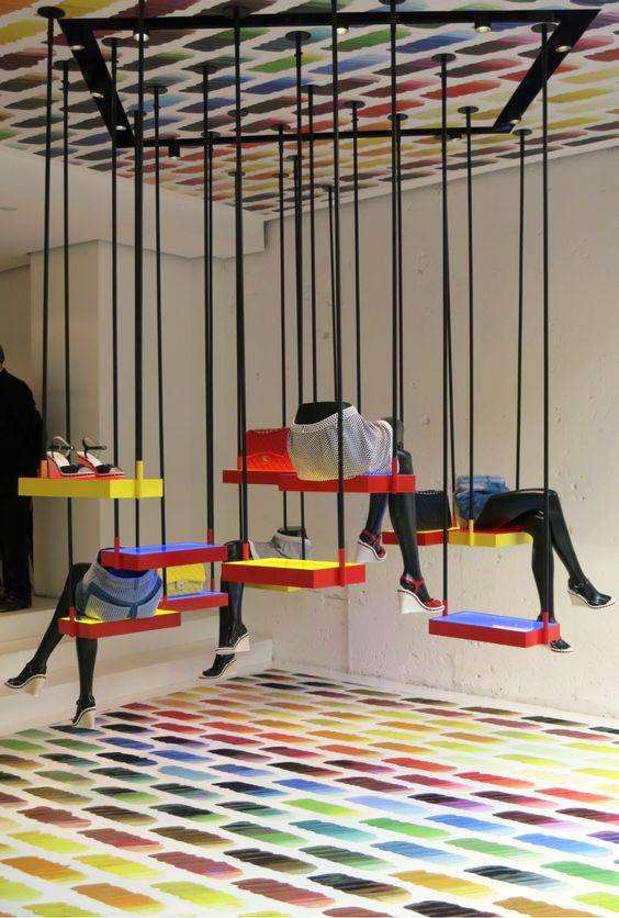 Rainbow brights on the floor and ceiling, plus an unconventional swing set make for a window display at Chanel, Paris.