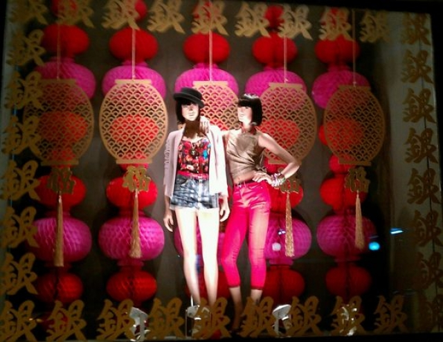 Pop culture fashion in a window display with gold elements and colored paper lanterns to represent the Chinese New Year celebration.