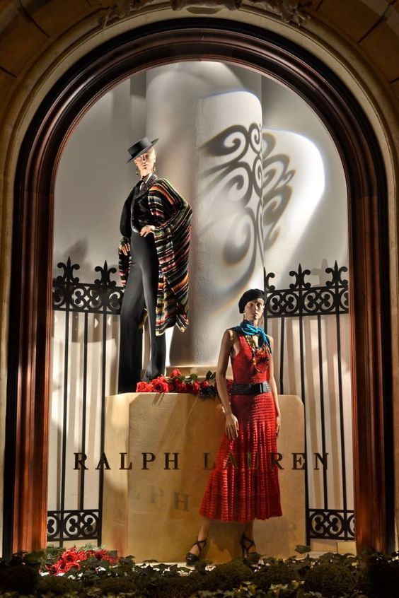 Window display with two mannequins, using props such as a fence and a column, decorated with red flowers. Ralph Lauren window in Paris.