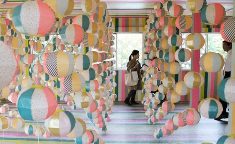 Picture from the MT Tape Installation in Japan, displayed are wires filled with striped colorful balls.