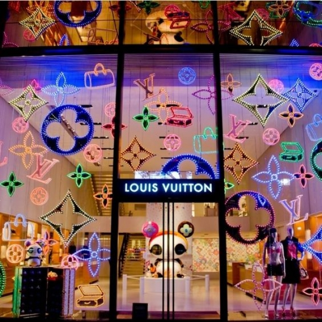 Kitsch neon Louis Vuitton symbols all over the glass used for a store display in Tokyo.