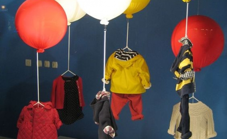 Window decoration for Step Styles in London using large balloons with the merchandise hanging from them.