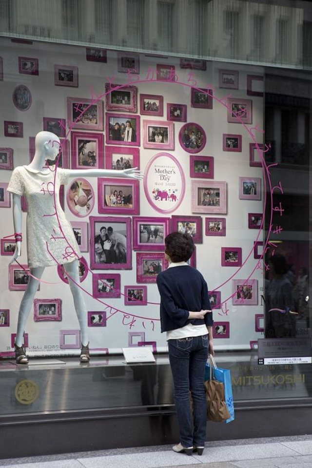 Touching visual merchandise display made with photos in pink frames for the celebration of Mother's Day.