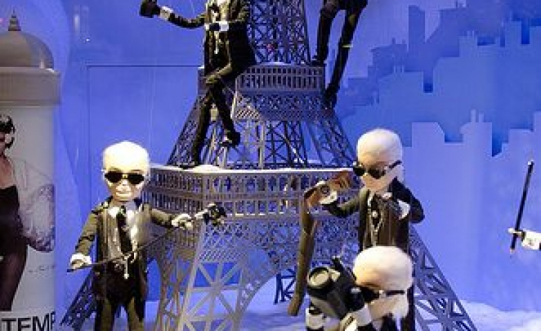 Christmas in Paris with a Eiffel Tower props and the blue city behind, seen at Printemps in Paris, France.
