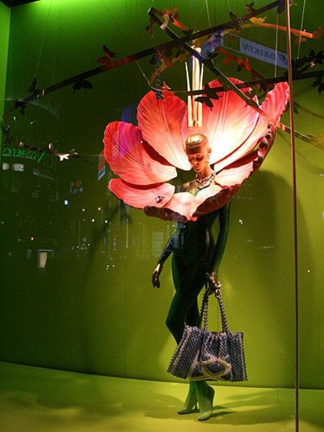 Flower inspired visual merchandise display with giant petals placed around the head of the mannequin, seen in Tokyo.